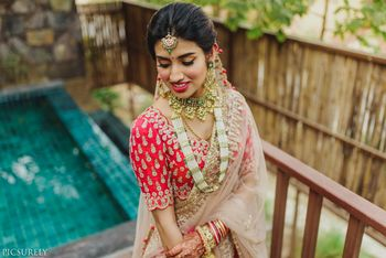 Unique simple bridal look in red blouse and layered jewellery