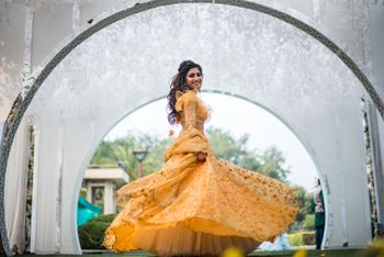 Photo of Bride twirling in yellow mehendi lehenga with ruffled blouse