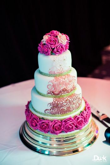 Photo of white and magenta wedding cake with roses