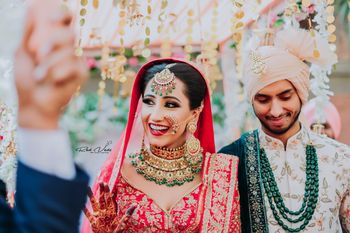 Photo of happy bride shot in green jewellery and red lehenga