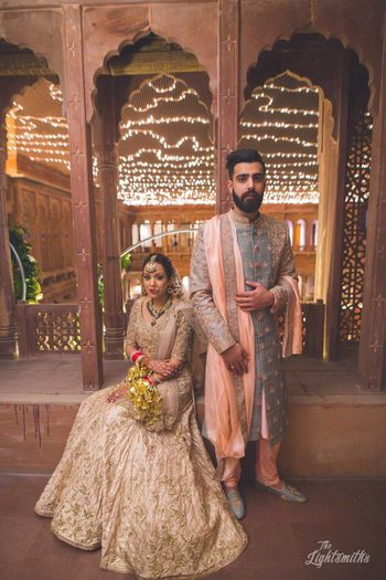 Photo of Bride in beige lehenga and groom in slate blue sherwani