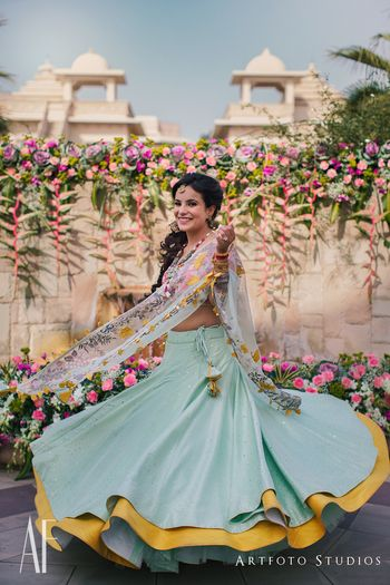 Bride twirling in mustard and blue mehendi lehenga