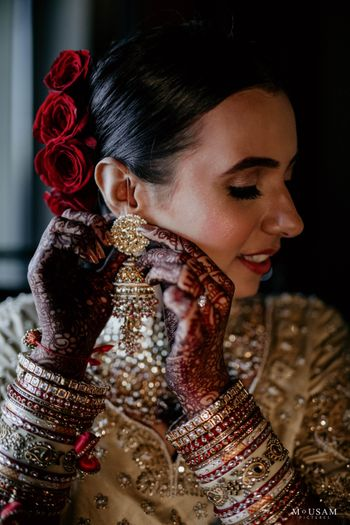 bridal shot wearing her gold earrings