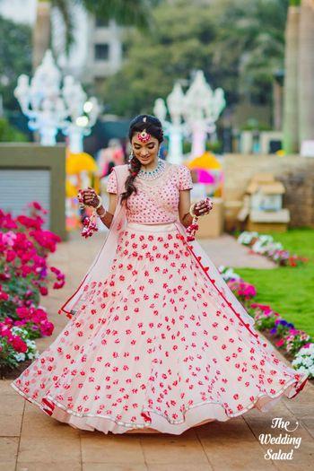 Bride showing off floral mehendi lehenga