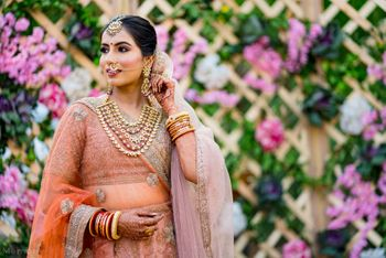 Photo of bride in peach bridal lehenga and unique necklace