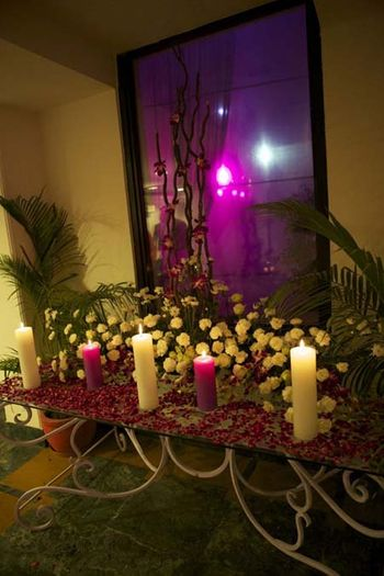 Photo of clustered table setting with candles and purple petals