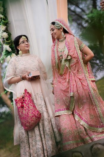 Sikh bride in pastel pink sharar with bridesmaid