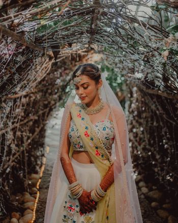 Bride wearing an ivory lehenga with double dupattas.