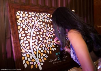 Photo of Guests leaving notes on a wishing tree poster for the couple