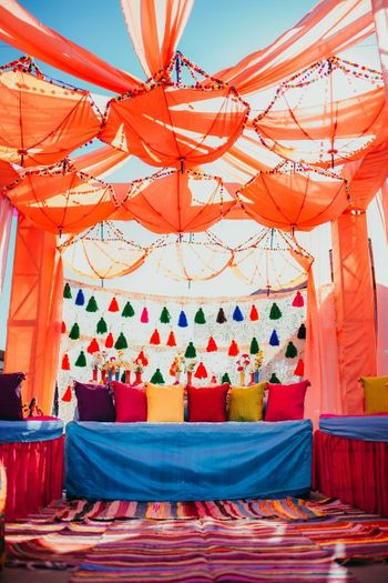 Colourful mehendi decor with tassels and hanging umbrellas