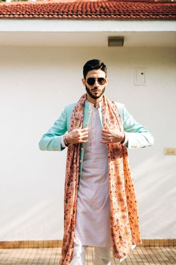 The groom on mehendi in a white kurta with blue jacket and multicoloured dupatta