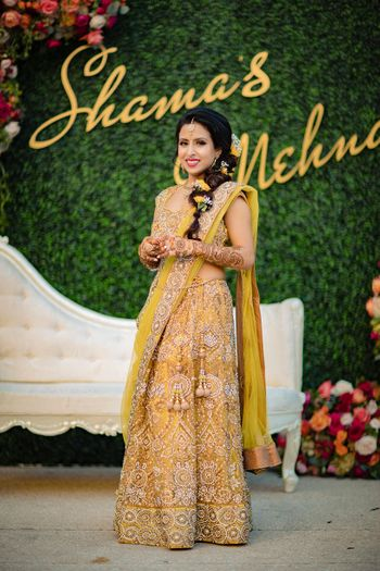 Photo of Bridal mehendi look in mustard lehenga and side braid with flowers