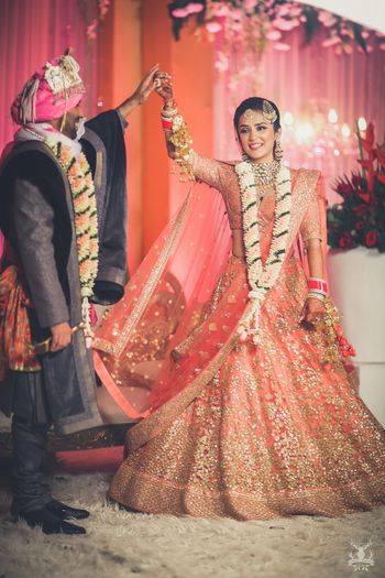 Photo of Peach and gold bridal lehenga on stage