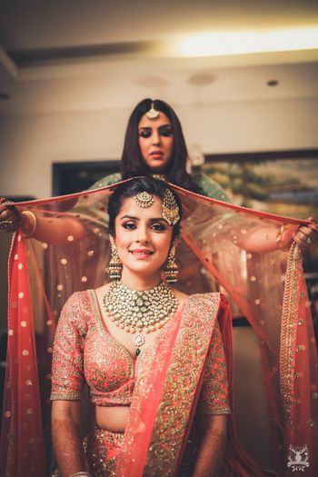 Photo of Bride with bridesmaid dupatta placing shot