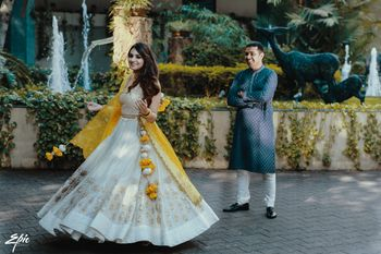 A bride in a blue lehenga twirls as her groom looks on
