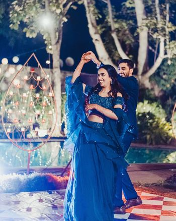 dancing couple shot with the bride in a blue cocktail lehenga