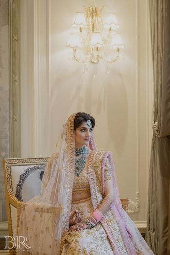 Photo of pastel pink bridal lehenga with unique blouse and green jewellery