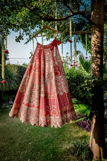 Bridal lehenga in red and white hues, hung on hangar