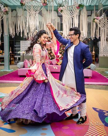 Couple portrait with bride twirling in purple lehenga