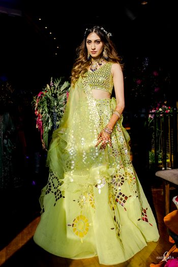 bride in lime green lehenga on her mehendi with open wavy hair