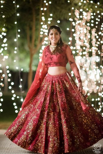 Bride twirling in maroon sequin work lehenga