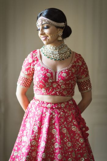 A bride in a red lehenga with a gold choker
