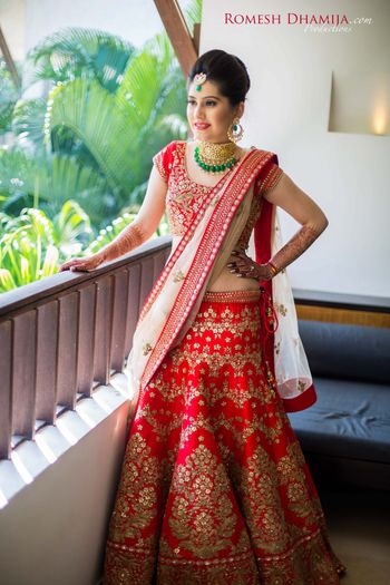 Red and white bridal lehenga with green jewellery