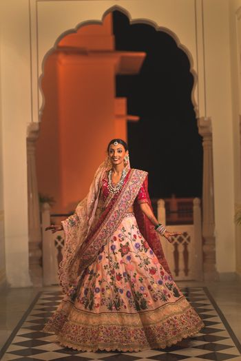 A bride in a custom-made lehenga twirling happily