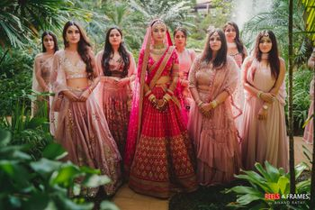 Photo of Bride in pink lehenga with coordinated bridesmaids in light pink outfits