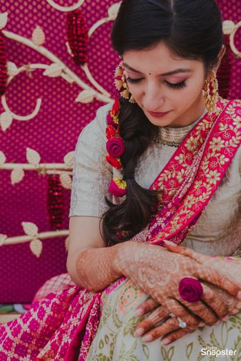 A bride in a pink and grey outfit for her haldi