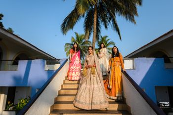 Photo of A bride in a light pink lehenga poses with her bridesmaids on her wedding day