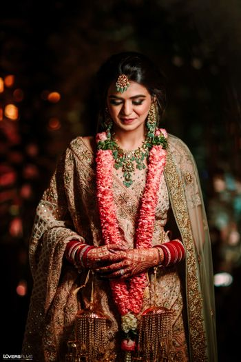 Bride wearing a pastel pink lehenga with emerald jewellery.