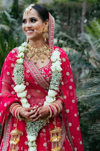 Bride in beautiful jewellery and red lehenga.