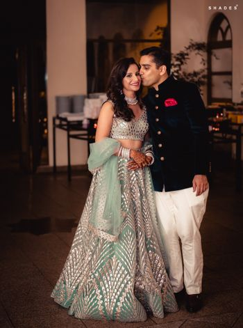 Photo of A bride in a shimmer lehenga posing with her groom-to-be at their sangeet