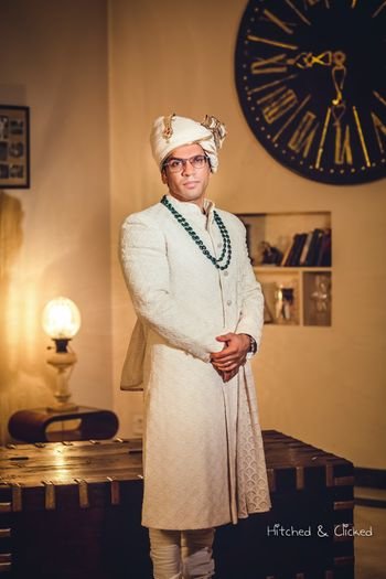 Groom in off white sherwani and green necklace