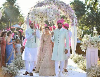 A bride enters under a gorgeous floral phoolon ki chaadar