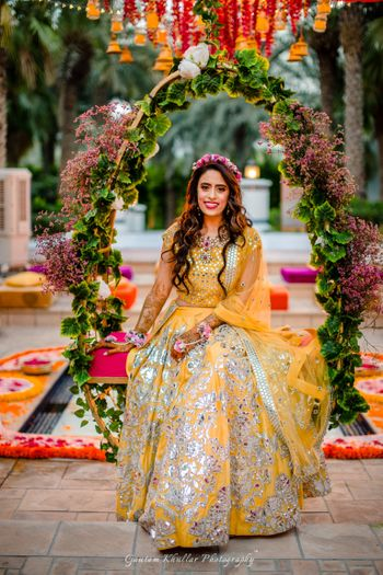 Photo of Stunning silver and yellow bridal lehenga with floral wreath for mehendi