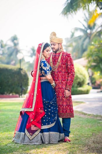 Photo of Offbeat bridal lehenga and groom in red