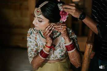Photo of A bride gets ready to put on her jewelry while getting her bun adorned with roses.