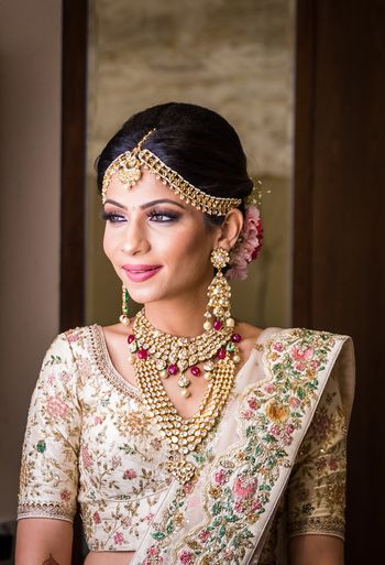 A bride poses in their ivory lehenga and unique jewelry