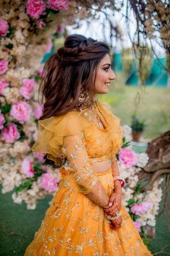 Photo of Open hair braided mehendi hairdo with yellow lehenga