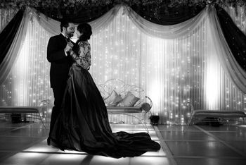 Photo of beautiful stage backdrop with drapes and fairy lights