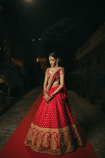 Photo of bride in classic red and gold sabyasachi lehenga