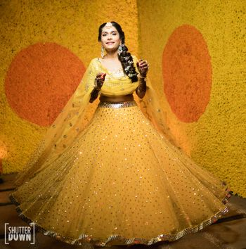 A bride twirling in a yellow lehenga in front of a wall decorated with marigold flowers