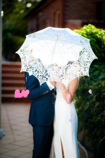 Photo of pre wedding shoot with lace umbrella and hanging pink paper hearts swishing through the wind