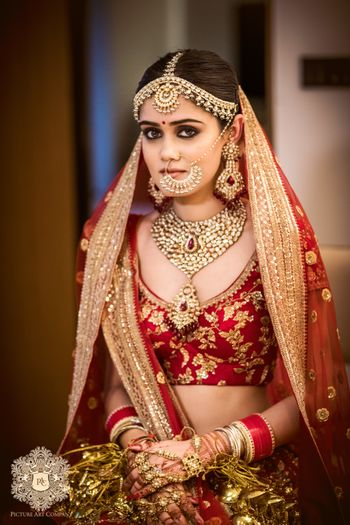 Bride in red floral embroidery lehenga and matching jewellery