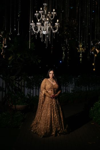Bride on her cocktail in a gold lehenga