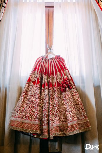 Red bridal lehenga hung on hanger