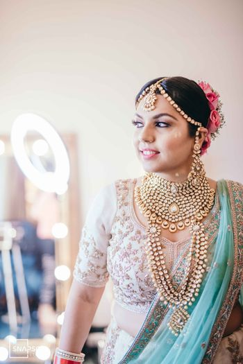 A happy bride in heavy gold jewellery.
