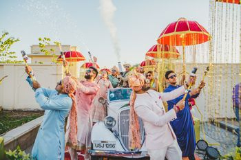 Photo of Groom entry in vintage car and party poppers